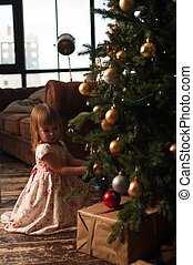 Cute girl sitting near Christmas tree with gifts