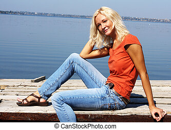 Cute girl sitting on a river bank