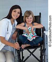 Cute girl sitting on a wheelchair with a female doctor