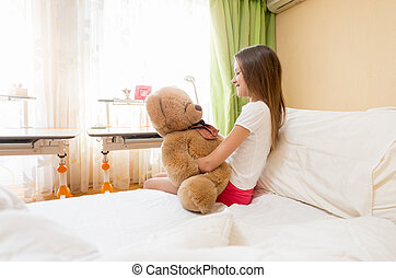 Cute girl sitting on bed and hugging her teddy bear