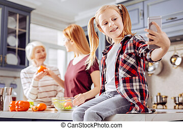 Cute girl sitting on the table and taking selfies while her relatives cooking