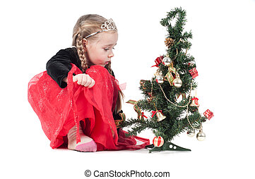 Cute girl sitting with christmas tree