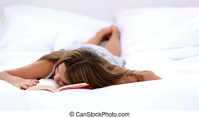 Cute girl sleeping on her book at home on her bed