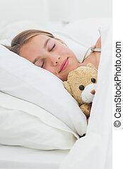 Cute girl sleeping with her teddy bear