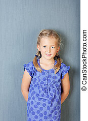 Cute Girl Smiling While Standing Against Blue Wall