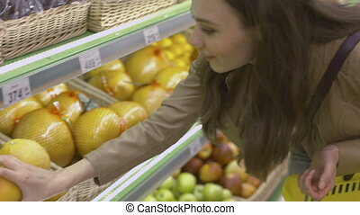 Cute girl standing near the shelves with fruits in the supermarket