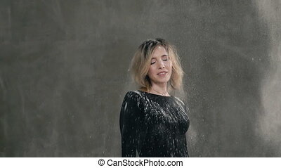 Cute girl standing on the background of a gray wall in the studio on which the grains of white powder or flour are shaken looking at the camera and smiles