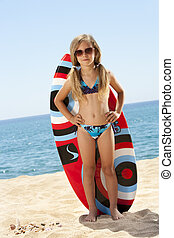 Cute girl standing with surfboard on beach.