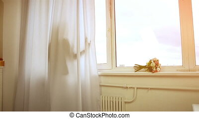 cute girl stands behind the curtain at the window comes and looking into the camera
