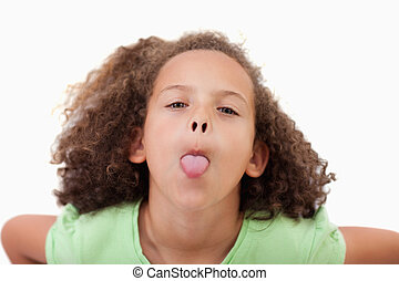Cute girl sticking out her tongue against a white background
