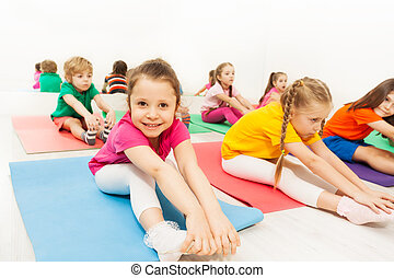 Portrait of cute five years old girl stretching on floor in the gym center with her friends