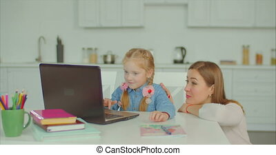 Cute girl studying with laptop with mother's help - Cheerful...