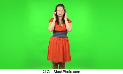 Cute girl suffering from headache from fatigue. Chubby girl in a coral dress with straight hair medium length and light eyes on green screen at studio