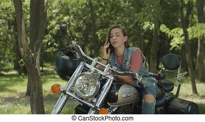 Cute girl talking on phone leaning on motorbike - Charming...