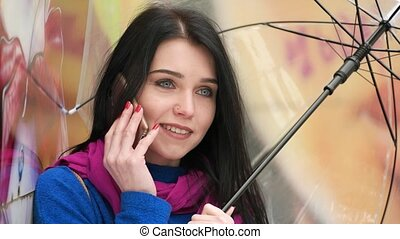 Cute girl talking on the phone in a Sunny day under an umbrella