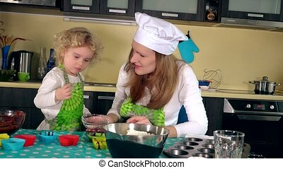 Cute girl taste sweets with mother in kitchen. Woman with daughter cook muffins