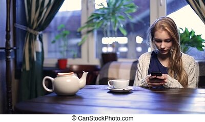 Cute girl typing message on smart phone in cafe