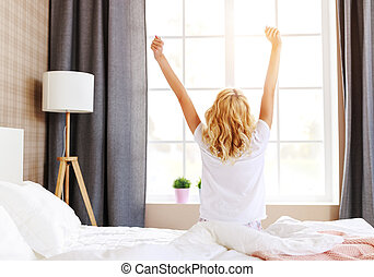 cute girl wakes up in her bedroom and stretching in the morning