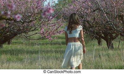 Cute girl walking in the flowering peach garden