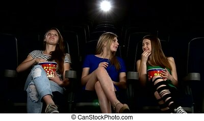 Cute girl watching movie in cinema theater. and eating popcorn