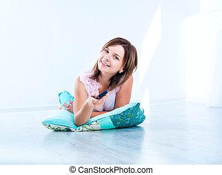 cute girl watching TV lying on the floor