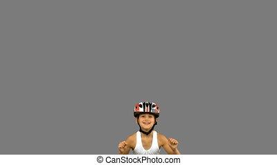 Cute girl wearing a bike helmet and jumping on grey screen...