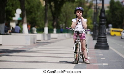 Cute girl wearing helmet and then rides a bicycle in park in sunshine day.