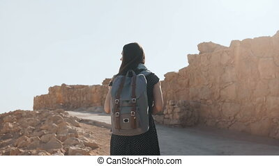 Cute girl with backpack walks along ancient ruins. Pretty...