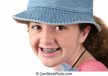 A closeup of a cute teenaged girl with braces