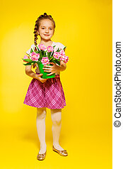 Cute girl with braid hold pail and pink tulips