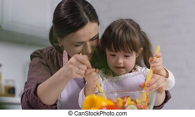 Cute girl with down syndrome cooking with mother