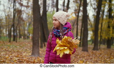 Cute girl with fallen leaves strolling in autumn park -...