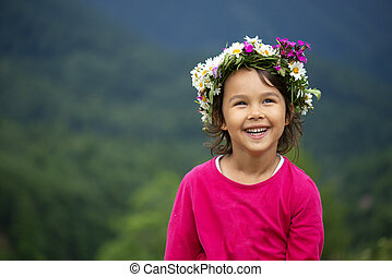 cute girl with flower crown smiling and having fun on meadow