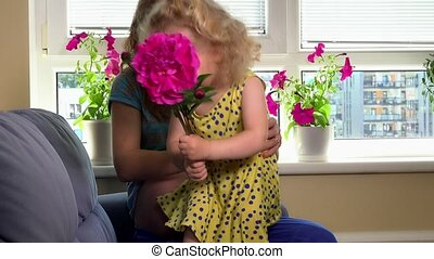 Cute girl with flower stroke her pregnant mother tummy with...