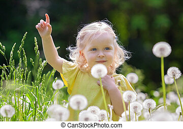 Cute girl with fluffy blond hair in a summer meadow among white dandelions