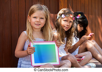 Cute girl with friends showing blank tablet.
