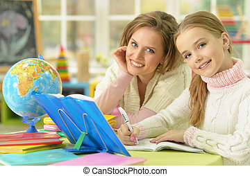 Cute girl with her mother doing homework