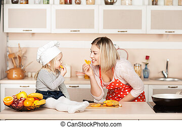 Cute girl with her mother eating orange while cooking