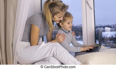 Cute girl with her mother using laptop computer