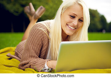 Cute girl with laptop in park