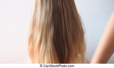 Cute girl with long blond hair, back view on light...