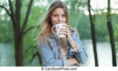 Cute girl with long hair holds a cup of tea or coffee in hands against the blurred nature background. Pretty woman in jeans jacket smiles and drinks beverage. Slow motion panning.