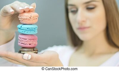 Cute girl with macaroons on black background