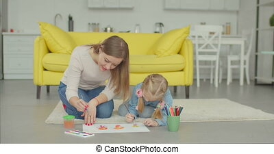 Cute girl with mother making painting at home
