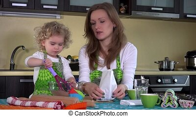 Cute girl with mother mixing chocolate flour in glass bowl on kitchen table