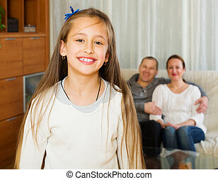 Cute girl with parents in background