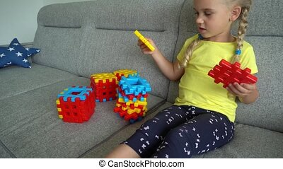 Cute girl with pigtails playing with constructor parts on sofa. Gimbal motion