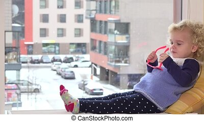 Cute girl with pink sunglasses sit on window sill and snowflakes fall outside