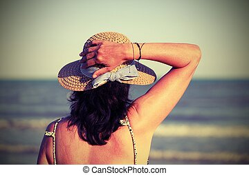 girl with straw hat by the sea in summer