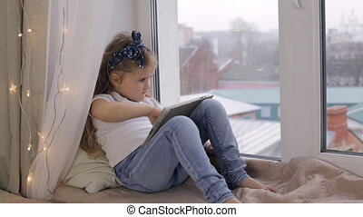 Cute girl with tablet sitting on a window sill